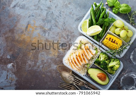 Healthy green meal prep containers with chicken, rice, avocado and vegetables overhead shot with copy space - Shutterstock ID 791065942