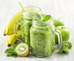 healthy green smoothie in a jar mug of spinach, kiwi, banana and apple on a wooden background