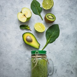 Healthy green smoothie in mason jar and ingredients. Superfoods, detox, diet, healthy food. Lime, apple, spinach, avocado and lime. Green food background.