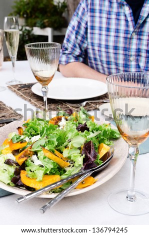Healthy green vegetable salad served on a table set for a party outdoors in the garden