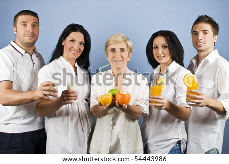 Healthy group of friends people or family persons  standing in a line and holding different  fruits, fresh orange juice or milk in glasses,all  people wearing white clothes