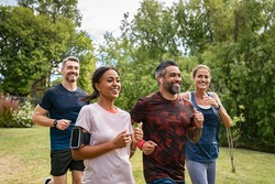 Healthy group of multiethnic middle aged men and women jogging at park. Happy mixed race couples running together. Mature friends running together outdoor.
