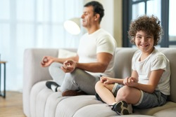 Healthy habit. Happy latin school boy smiling at camera while meditating together with his father on a couch at home