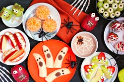 Healthy Halloween fruit snacks. Assorted fun, spooky treats. Top view table scene over a black stone background.