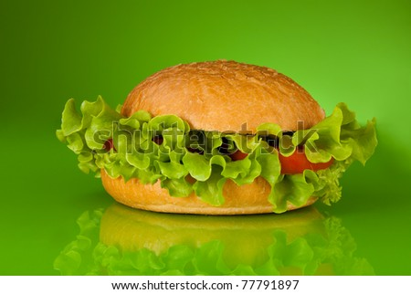 Healthy hamburger without meat only with tomatoes and salad on green background