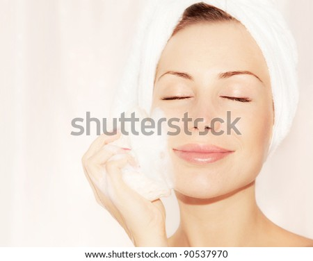 Healthy happy girl taking bath, beautiful young female cleaning face skin,  portrait over soft light background, hygiene and day spa