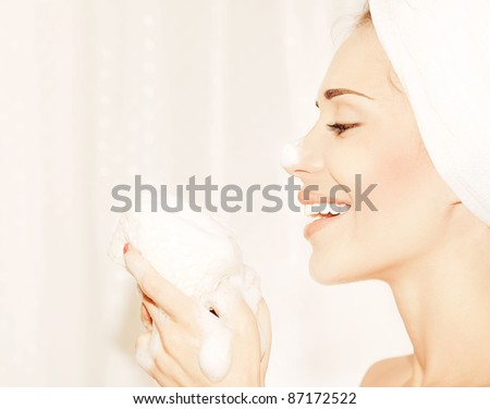 Healthy happy girl taking bath, profile portrait of a beautiful young female cleaning face skin, hygiene and day spa