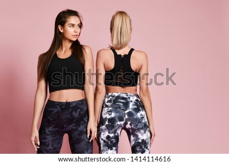 Healthy happy smiling sport girls in multi-colored comfortable sportswear after workout talk and laugh on pink background with free text copy space