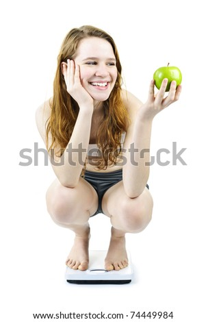 Healthy happy young woman holding apple on bathroom scale isolated on white