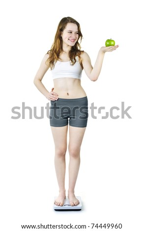 Healthy happy young woman holding green apple standing on bathroom scale