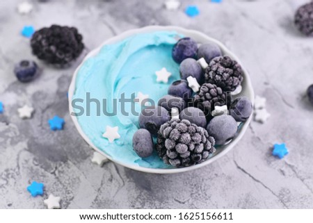 Healthy healthy cegan banana cream fruit smoothie bowl with natural blue spirulina powder topped with blackberry and blueberry fruits