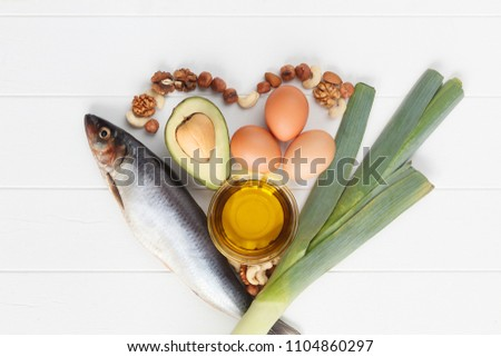 Healthy heart food with fish, avocado, eggs, leek, olive oil, nut on white wooden kitchen table or background. Top view. High in omega 3. Super food high vitamin D and dietary fiber for healthy food. #1104860297