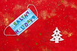 Healthy Holidays Christmas and New Year concept banner during coronavirus COVID-19 time. Top view of disposable protective face mask with letters on red glittered background