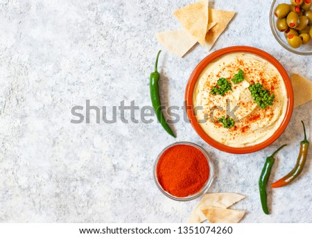 Healthy homemade hummus served with paprika powder, pita bread, olives and parsley. Middle Eastern cuisine, Israeli cuisine, Levanese cuisine, Levantine cuisine. Light background. Top view #1351074260