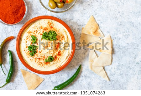 Healthy homemade hummus served with paprika powder, pita bread, olives and parsley. Middle Eastern cuisine, Israeli cuisine, Levanese cuisine, Levantine cuisine. Light background. Top view