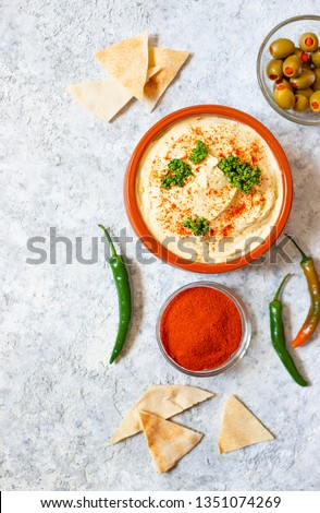 Healthy homemade hummus served with paprika powder, pita bread, olives and parsley. Middle Eastern cuisine, Israeli cuisine, Levanese cuisine, Levantine cuisine. Light background. Top view #1351074269