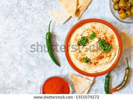 Healthy homemade hummus served with paprika powder, pita bread, olives and parsley. Middle Eastern cuisine, Israeli cuisine, Levanese cuisine, Levantine cuisine. Light background. Top view #1351074272