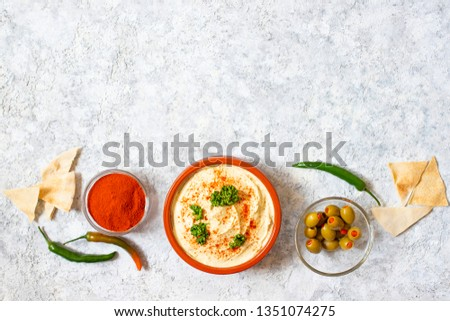 Healthy homemade hummus served with paprika powder, pita bread, olives and parsley. Middle Eastern cuisine, Israeli cuisine, Levanese cuisine, Levantine cuisine. Light background. Top view #1351074275
