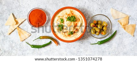 Healthy homemade hummus served with paprika powder, pita bread, olives and parsley. Middle Eastern cuisine, Israeli cuisine, Levanese cuisine, Levantine cuisine. Light background. Top view #1351074278