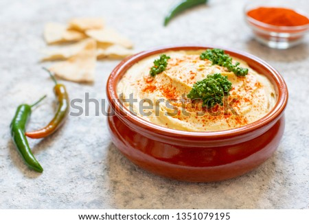 Healthy homemade hummus served with paprika powder, pita bread, olives and parsley. Middle Eastern cuisine, Israeli cuisine, Levanese cuisine, Levantine cuisine. Light background. Close-up view