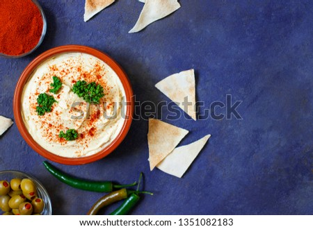 Healthy homemade hummus served with paprika powder, pita bread, olives and parsley. Middle Eastern cuisine, Israeli cuisine, Levanese cuisine, Levantine cuisine. Dark background. Top view