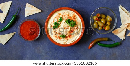 Healthy homemade hummus served with paprika powder, pita bread, olives and parsley. Middle Eastern cuisine, Israeli cuisine, Levanese cuisine, Levantine cuisine. Dark background. Top view #1351082186