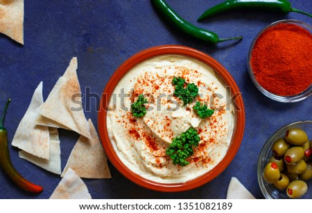 Healthy homemade hummus served with paprika powder, pita bread, olives and parsley. Middle Eastern cuisine, Israeli cuisine, Levanese cuisine, Levantine cuisine. Dark background. Top view #1351082189
