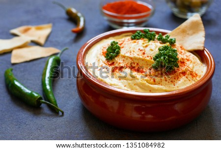 Healthy homemade hummus served with paprika powder, pita bread, olives and parsley. Middle Eastern cuisine, Israeli cuisine, Levanese cuisine, Levantine cuisine. Dark background. Closeup view #1351084982