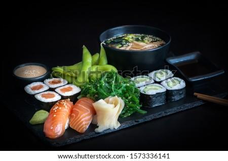 Healthy japanese bento lunch with salmon maki, cucumber maki, nigiri salmon sushi, seaweed salad, edamame and miso soup tofu on black background.