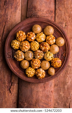 Healthy Laddoo using roasted Peanuts, Sesame and split Daliya with jaggery, served in a wooden plate, selective focus