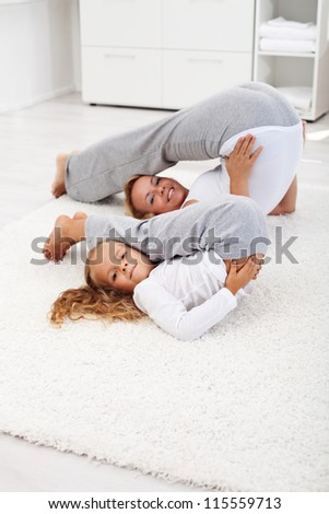 Healthy life concept - woman and little girl doing gymnastic exercise at home