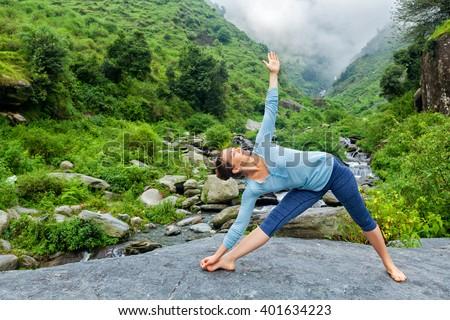Healthy life exercise concept - Woman doing Ashtanga Vinyasa yoga asana Utthita trikonasana - extended triangle pose outdoors at waterfall in Himalayas