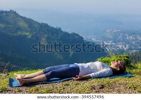 Healthy life exercise concept - Woman relaxes in yoga asana Savasana - corpse pose outdoors in Himalayas. Himachal Pradesh, India