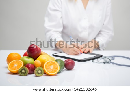 Healthy life style concept, doctor writing, diet and losing weight, shallow focus