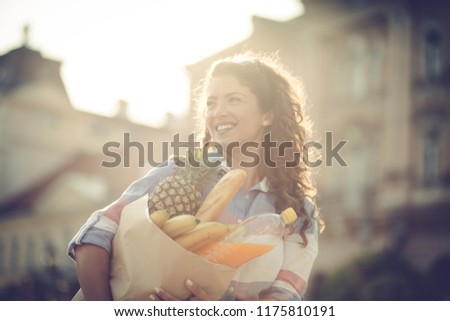 Healthy life. Woman walking trough city park and holding bag with fruit. Close up. Copy space.