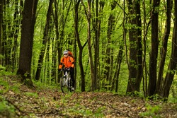 healthy lifestyle and fitness concept with mount bike man on trail in the forest