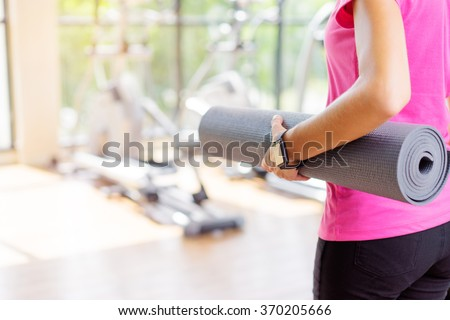Healthy lifestyle and sport. Close up of young woman holding mat in gym.