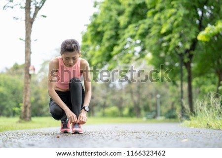 Healthy lifestyle and sport concepts, Fitness sport woman runner jogging ,girl runner jogging exercise benefit workout in a Park, tying laces of running shoes before training. #1166323462