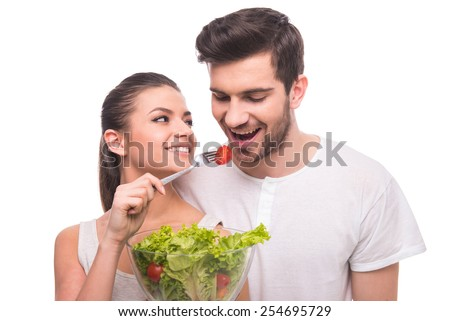 Healthy lifestyle. Beautiful couple are eating salad isolated on white background. #254695729