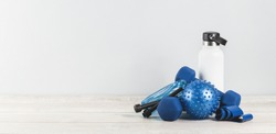 Healthy lifestyle blue gender neutral sports accessories grouped around white water bottle flask on white grey wood. Fitness and exercise monochrome items banner with copy space