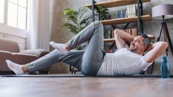 Healthy lifestyle concept. Adult man making abdominal exercises at home