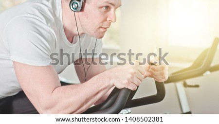 Healthy lifestyle concept. Close up portrait Young sporty man in white t-shirt and shorts is exercising cycling in the gym for group exercises. Cardio training