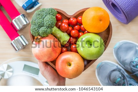 Healthy lifestyle concept, eating clean food good health dietary in heart dish with sporty aerobic body exercise workout training class gym equipment, weight scale and sports shoes in fitness center #1046543104