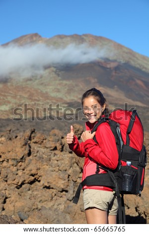 Healthy lifestyle concept- happy woman hiker giving thumbs up before summit hike. Beautiful young Asian / Caucasian model. Shows Pico Viejo, Teide National Park, Tenerife with lots of copyspace.