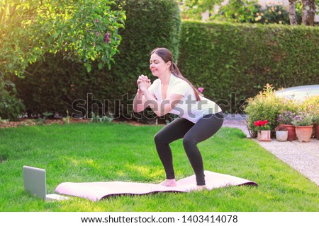 Healthy lifestyle. Exercising at home. Doing fitness online. Beautiful young woman doing sport in garden outdoors following guide of online tutorial or trainer on laptop. Beginner