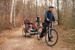 Healthy lifestyle - family biking in forest or park.People are riding bicycles in city park during spring or early fall time. Man pulls the sport trailer stroller by his bike with two sons. Happiness.