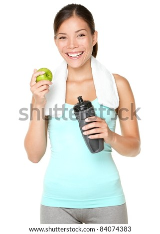 Healthy lifestyle - fitness woman eating apple smiling happy looking at camera. Pretty mixed race Caucasian Asian woman isolated on white background.