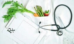 Healthy lifestyle, food is medicine, concept flatlay with fruit and vegetables in pocket of white doctor's coat with clipboard and stethoscope.