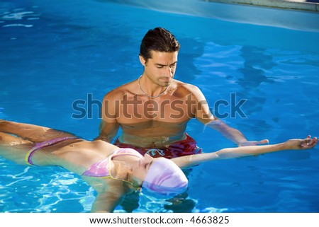 Healthy lifestyle: girl taking swimming lessons in a swimming pool