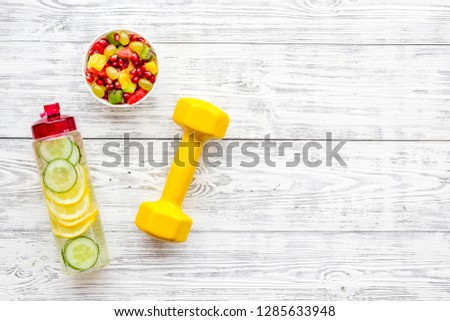 Healthy lifestyle, healthy habits. Detox water, fruit salad, sport equipment dumbbells on white wooden background top view copy space